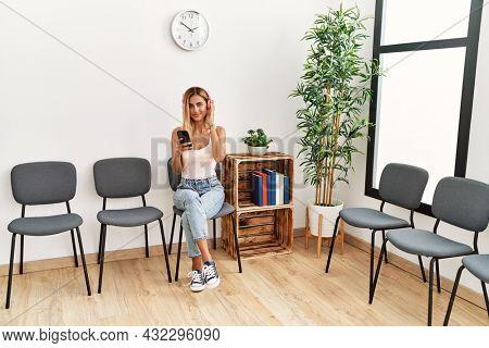 Young caucasian girl listening to music using smartphone and headphones at waiting room.