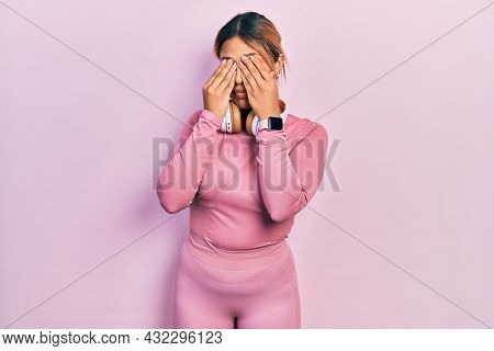 Beautiful hispanic woman wearing gym clothes and using headphones rubbing eyes for fatigue and headache, sleepy and tired expression. vision problem