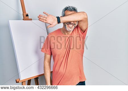 Handsome middle age man with grey hair standing by painter easel stand smiling cheerful playing peek a boo with hands showing face. surprised and exited