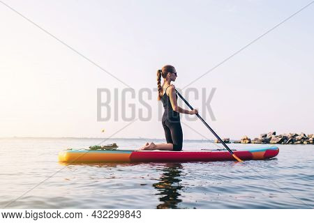Close-up Of A Girl Floating On A Sup Board. The Concept Of Water Sports, Relaxation And Self-immersi