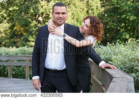 Portrait Of A Couple In Love. A Middle Eastern Man In A Business Suit With His Curly-haired Wife In