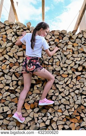 Beautiful Girl With Long Hair In White T-shirt And Shorts Against Background Of Pile Of Firewood. Сo