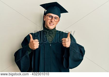 Young caucasian man wearing graduation cap and ceremony robe success sign doing positive gesture with hand, thumbs up smiling and happy. cheerful expression and winner gesture.