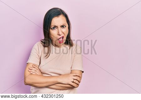 Middle age hispanic woman with arms crossed gesture in shock face, looking skeptical and sarcastic, surprised with open mouth