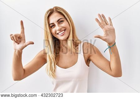 Blonde beautiful young woman standing over white isolated background showing and pointing up with fingers number seven while smiling confident and happy.