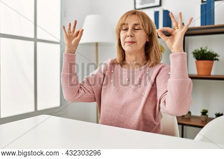 Middle age caucasian woman wearing casual clothes sitting on the table at home relax and smiling with eyes closed doing meditation gesture with fingers. yoga concept.