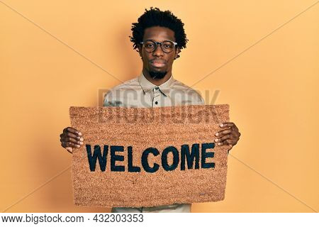 Young african american man holding welcome doormat relaxed with serious expression on face. simple and natural looking at the camera.