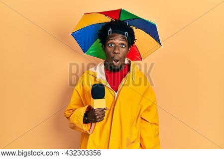 Young african american journalist man wearing yellow raincoat and umbrella cap scared and amazed with open mouth for surprise, disbelief face