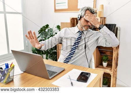 Middle age hispanic business man working at the office wearing operator headset covering eyes with hands and doing stop gesture with sad and fear expression. embarrassed and negative concept.