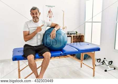 Middle age hispanic man at pain recovery clinic holding pilates ball pointing aside worried and nervous with forefinger, concerned and surprised expression