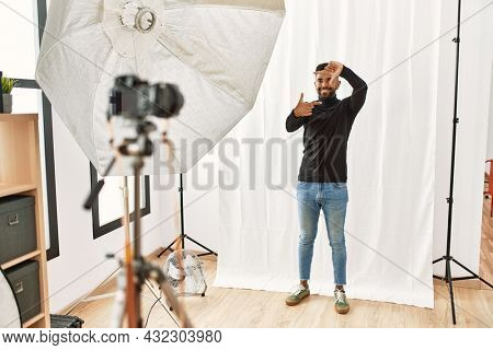Young hispanic man with beard posing as model at photography studio smiling making frame with hands and fingers with happy face. creativity and photography concept.
