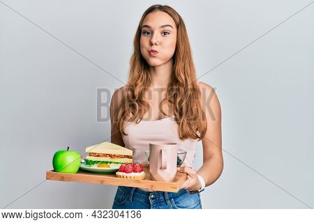 Young blonde woman holding tray with breakfast food puffing cheeks with funny face. mouth inflated with air, catching air.