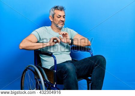 Handsome middle age man with grey hair sitting on wheelchair disgusted expression, displeased and fearful doing disgust face because aversion reaction.
