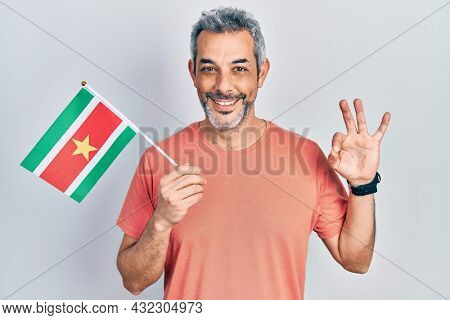 Handsome middle age man with grey hair holding suriname flag doing ok sign with fingers, smiling friendly gesturing excellent symbol