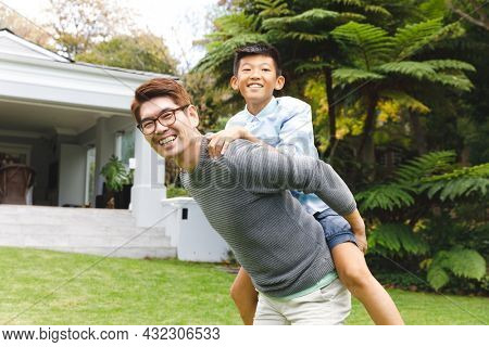 Portrait of happy asian father carrying his son and smiling outdoors in garden. family enjoying leisure time together at home.