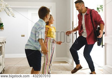 Happy caucasian father returning home with daughter and son smiling and greeting him at front door. hospitality and welcoming guests at home.