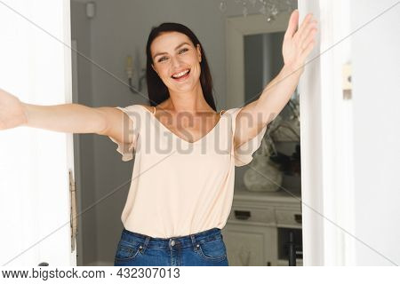 Portrait of happy caucasian woman standing at door and greeting a visitor with open arms. hospitality and welcoming guests at home