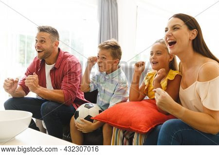 Excited caucasian parents on couch with daughter and son watching football match on tv and cheering. hospitality and welcoming guests at home