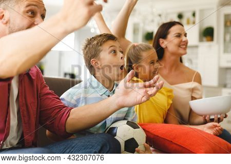 Excited caucasian parents on couch with daughter and son watching football match on tv and cheering. family entertainment and leisure time together at home.