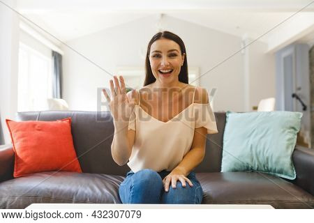 Caucasian woman sitting on couch having video call in living room, smiling and waving. keeping in touch, leisure time at home with communication technology.