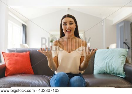 Happy caucasian woman sitting on couch having video call in living room, talking and gesturing. keeping in touch, leisure time at home with communication technology.