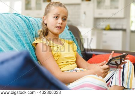 Caucasian girl sitting on couch and using tablet in living room. childhood leisure time, fun and discovery at at home using technology.