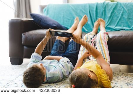 Caucasian brother and sister lying on living room floor using tablet. childhood leisure time, fun and discovery at at home using technology.