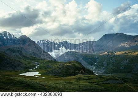 Dramatic Landscape With Mountain Lake And Big Glacier Under Cloudy Sky. Spot Of Sunlight On Mountain