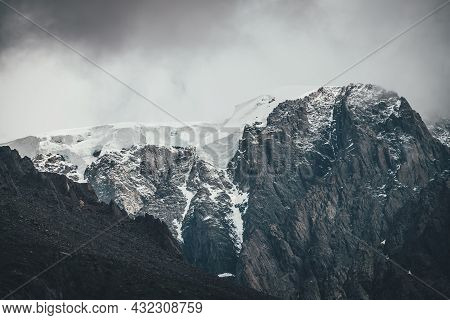 Dark Atmospheric Surreal Landscape With Dark Rocky Mountain Top In Low Clouds In Gray Cloudy Sky. Gr