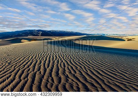 Mesquite Flat Sand Dunes is a part of Death Valley in California. The gentle slopes of the sand dunes are rippled by the wind. USA. Orange sunset in the desert. Concept of ecological and photo tourism