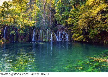 Plitvice Lakes Park in Croatia, Central Europe. The transparent shallow lake reflects the forest. Many picturesque waterfalls flow along the clay cliffs.