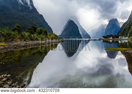 Mirror-smooth water of the Milford Sound fjord reflects mountains. Sunlight breaks through storm clouds. Land of goblins and hobbits. New Zealand. Concept of exotic, active and photographic tourism