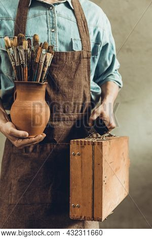 Man artist painter holding clay jug with paint brush. Painter artist and paintbrush in creative studio as art concept