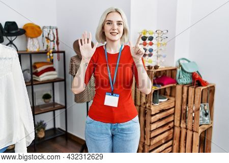 Young caucasian woman working as manager at retail boutique showing and pointing up with fingers number seven while smiling confident and happy.