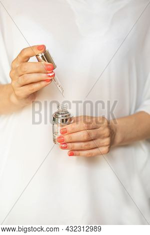 Female Hand Is Holding Dropper. Beauty Serum. Bottle Of Hyaluronic Acid With Pipette With Drop, Anti