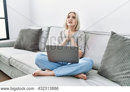 Young caucasian woman using laptop at home sitting on the sofa begging and praying with hands together with hope expression on face very emotional and worried. begging.