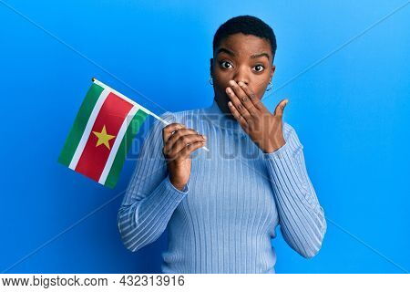 Young african american woman holding suriname flag covering mouth with hand, shocked and afraid for mistake. surprised expression