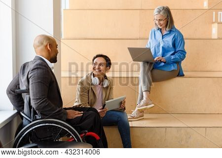 Afro american man manager in wheelchair working on laptop computer in the office with his colleagues talking