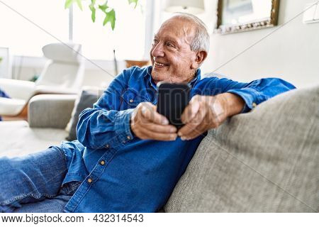Senior man with grey hair sitting on the sofa at the living room of his house using smartphone