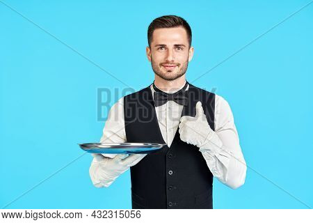 Elegant Young Waiter Holding Empty Silver Tray And Showing Thumbs Up Sign Over Blue Background