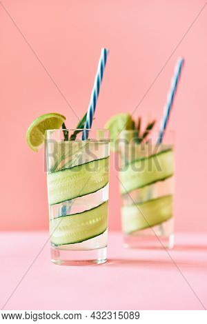 Cold Refreshing Cocktail With Lime, Cucumber, Rosemary And Ice In Glass On Pink Background