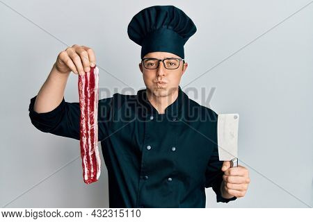 Handsome young man wearing chef uniform holding bacon and knife puffing cheeks with funny face. mouth inflated with air, catching air.