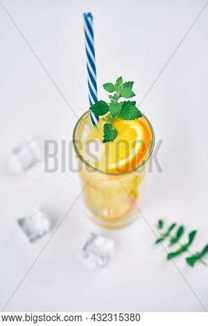 Cocktail With Orange Juice, Mint And Ice Cubes On White Background