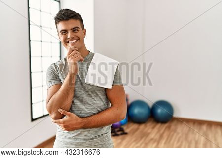 Young hispanic man wearing sportswear and towel at the gym looking confident at the camera smiling with crossed arms and hand raised on chin. thinking positive.