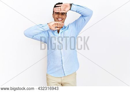 Young hispanic man wearing business shirt standing over isolated background smiling cheerful playing peek a boo with hands showing face. surprised and exited