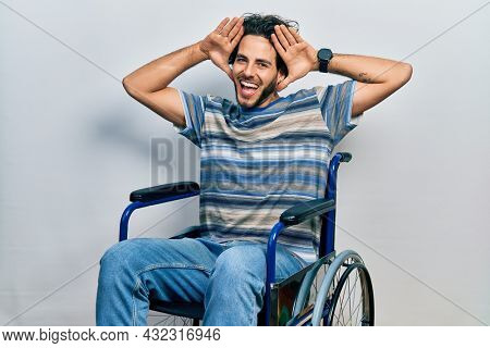 Handsome hispanic man sitting on wheelchair smiling cheerful playing peek a boo with hands showing face. surprised and exited