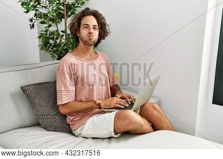 Young hispanic man sitting on the sofa at home using laptop puffing cheeks with funny face. mouth inflated with air, crazy expression.