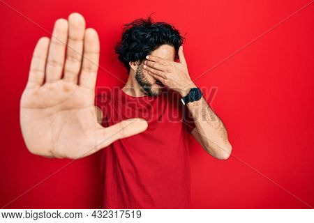 Handsome hispanic man wearing casual t shirt and glasses covering eyes with hands and doing stop gesture with sad and fear expression. embarrassed and negative concept.