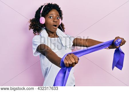 Young african american woman training arm resistance with elastic arm bands using headphones afraid and shocked with surprise and amazed expression, fear and excited face.
