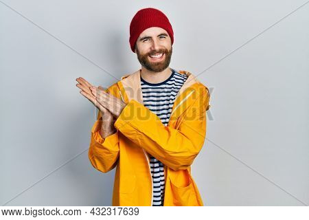 Caucasian man with beard wearing yellow raincoat clapping and applauding happy and joyful, smiling proud hands together